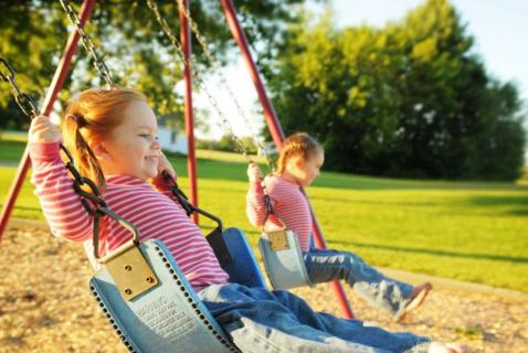 kids swinging in the late afternoon